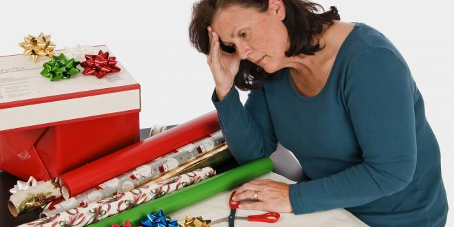 A very tired woman slouching in front of a pile of gift wrapping paper