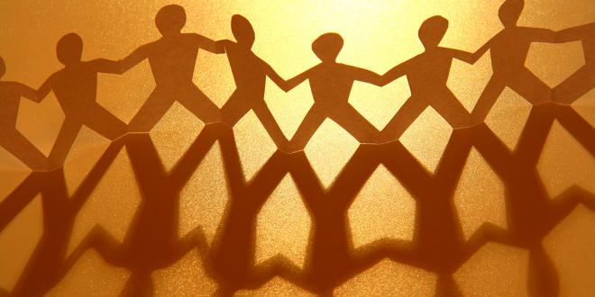 Paper figurines holding hands